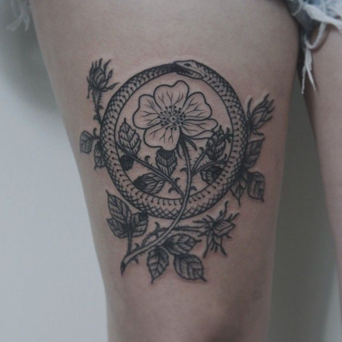 Geometric tattoo e un'idea con un fiore centro un serpente a cerchio che si morde la coda