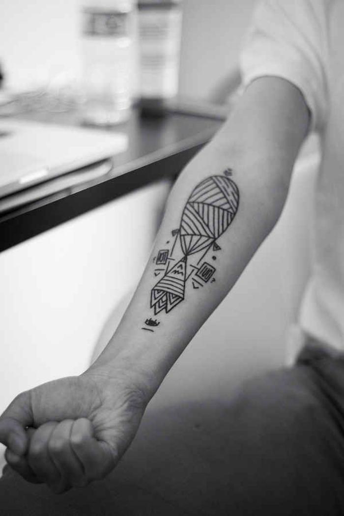 Idee tatuaggi uomo e un disegno di mongolfiera sull'avambraccio