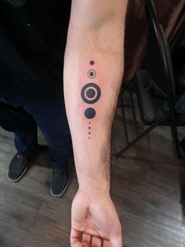 Il braccio di un uomo con un piccolo tattoo del sistema solare