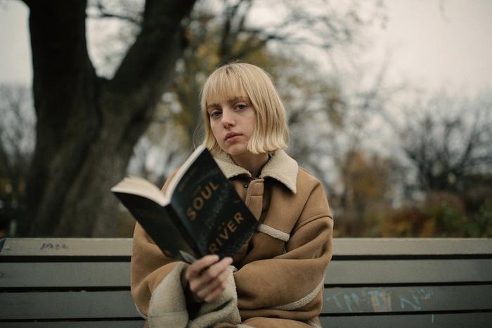 Idea per dei tagli capelli medi di colore biondo con frangia, ragazza con libro in mano seduta su una panchina