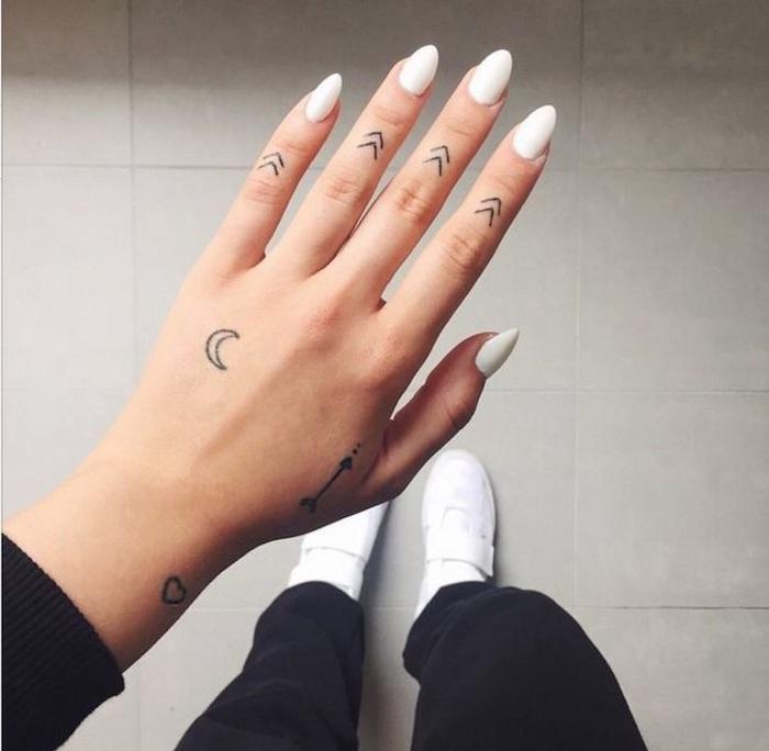 La mano di una donna con tattoo simbolici sulle dita