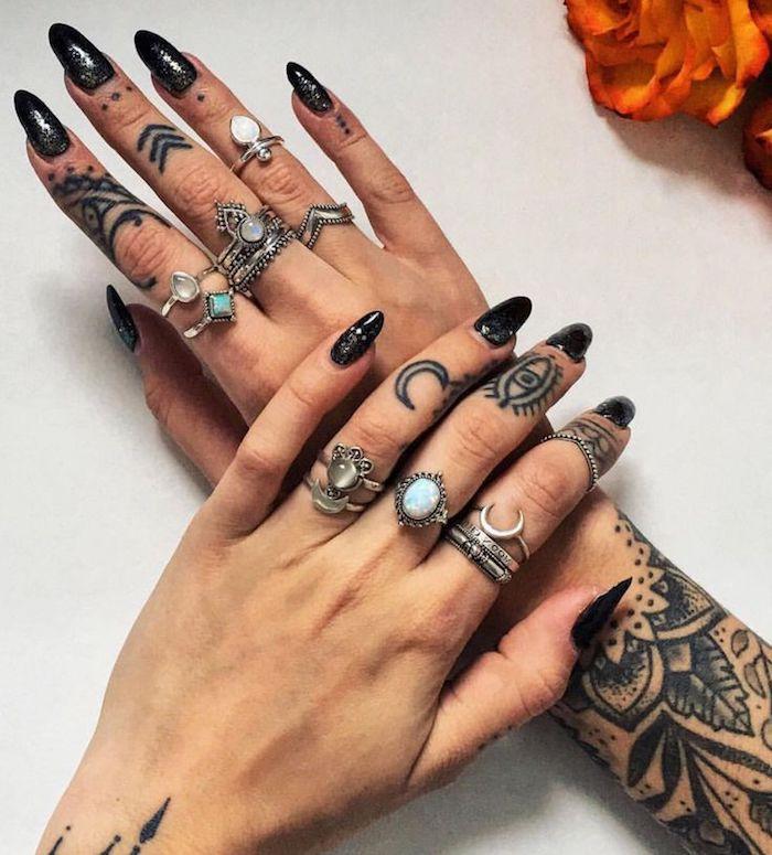 Mani tatuate di una donna con dei simboli, unghie a mandorla con smalto di colore nero