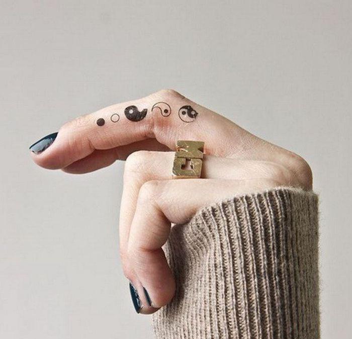 Il simbolo dello yang yin tatuato sul disto medio di una donna