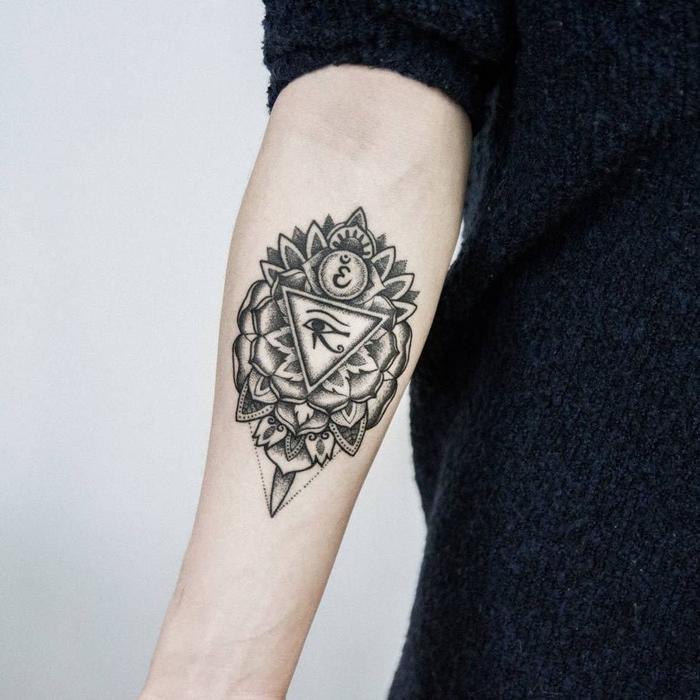 Simboli geometrici e un'idea tattoo con occhio di Ra sul braccio di una donna