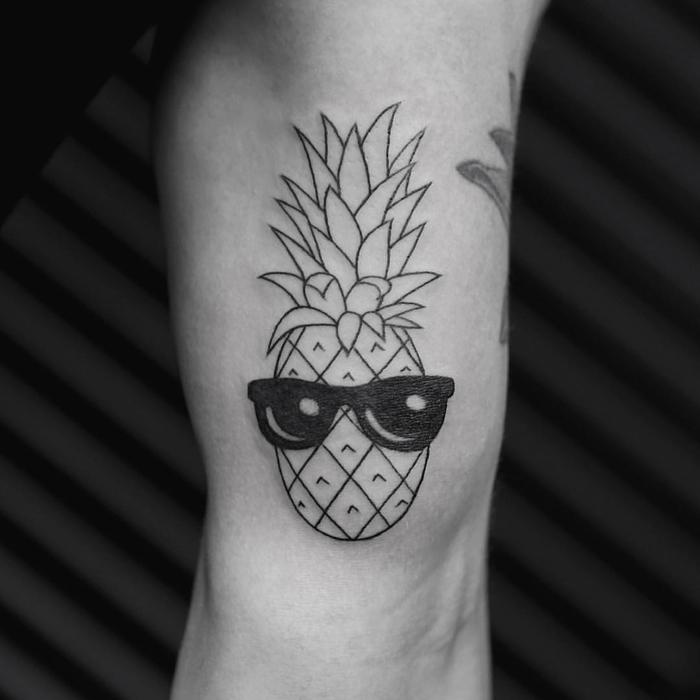 Tatuaggio geometrico e un'idea con un ananas divertente che indossa occhiali da sole