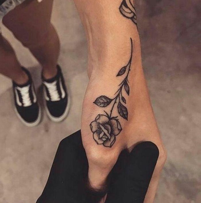 Idea per un tatuaggio sul dito pollice di una donna, tattoo di una rosa grande con le foglie