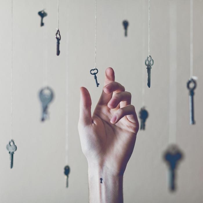 Tatuaggio immagini e un'idea con piccolo tattoo sul polso della mano con il disegno di una chiave