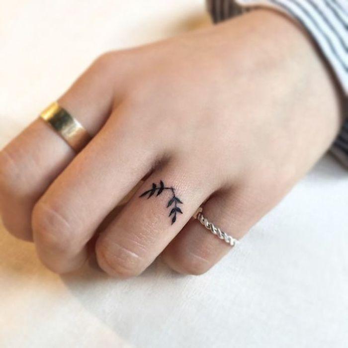 La mano di una donna con un piccolo tattoo floreale sul dito anulare
