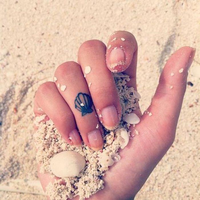 Tatuaggi sulle dita e un'idea con una piccola conchiglia sul dito anulare di una donna