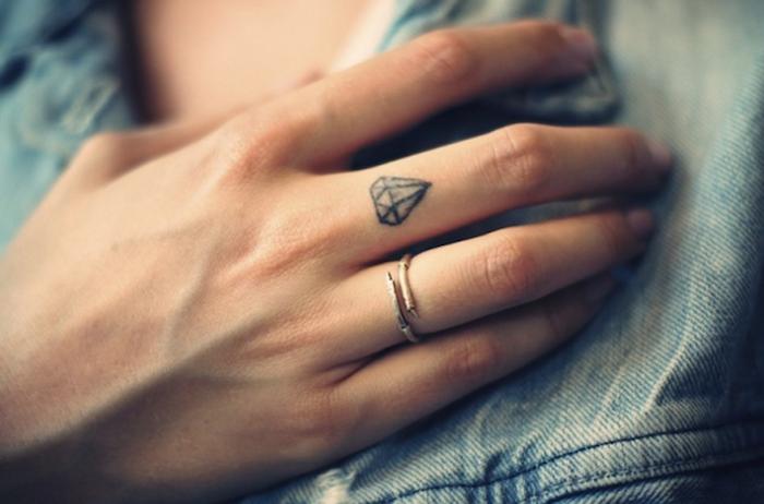 Tatuaggio sul dito medio mano di una donna con piccolo diamante