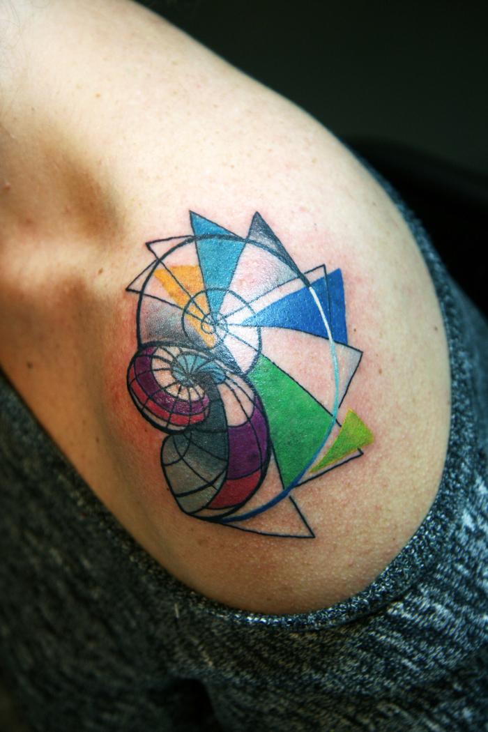 Simboli geometrici in un tattoo colorato sulla spalla di una donna