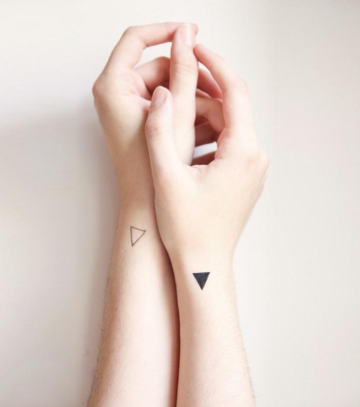 Tatuaggio geometrico e un'idea per due piccoli tatto triangoli sul polso della mano