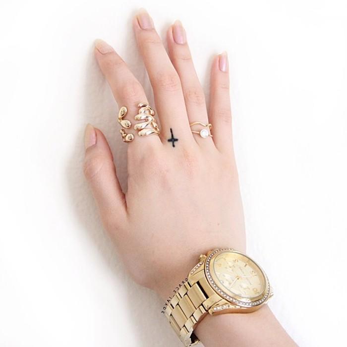 Tattoo sulle mani e un'idea di tatuaggio croce sulla mano di una donna