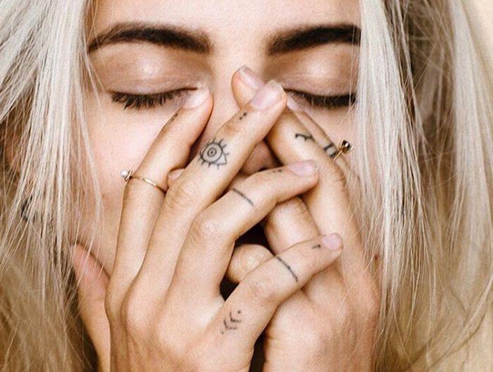 Tatuaggi sulle dita di una donna con simbolo occhio e frecce