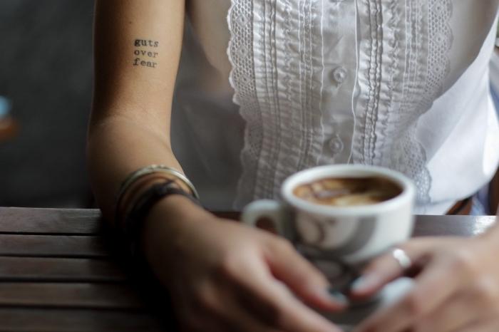 Tatuaggi piccoli e un'idea con una scritta sul braccio di una donna