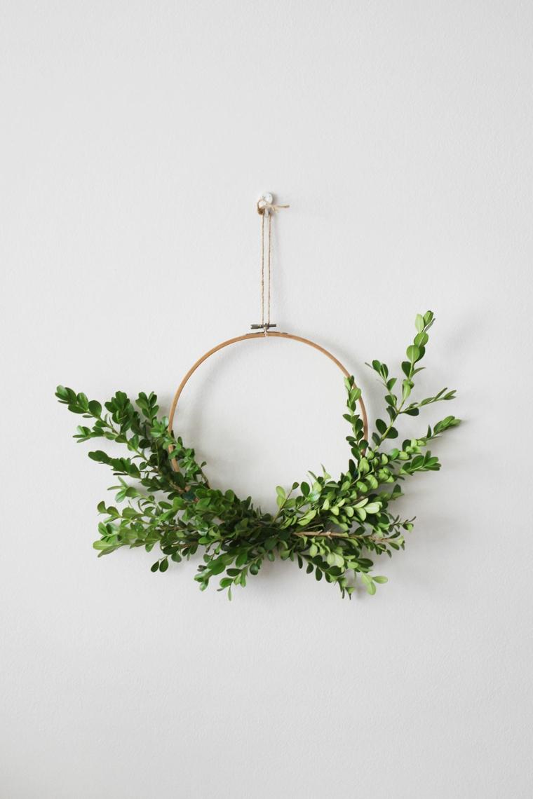 Ghirlande natalizie fai da te facili con un cerchio da ricamo e rametti con foglie verdi