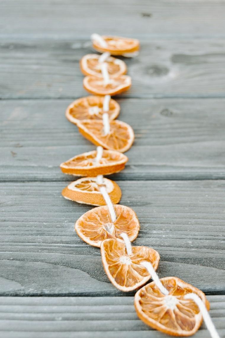Ghirlande natalizie fai da te facili e una con un filo bianco e fette di mandarini secche