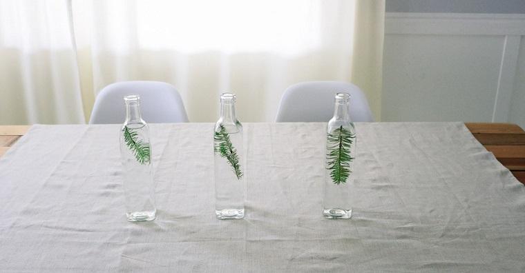 Tre bottiglie piene di acqua con rami verdi all'interno su una tovaglia bianca