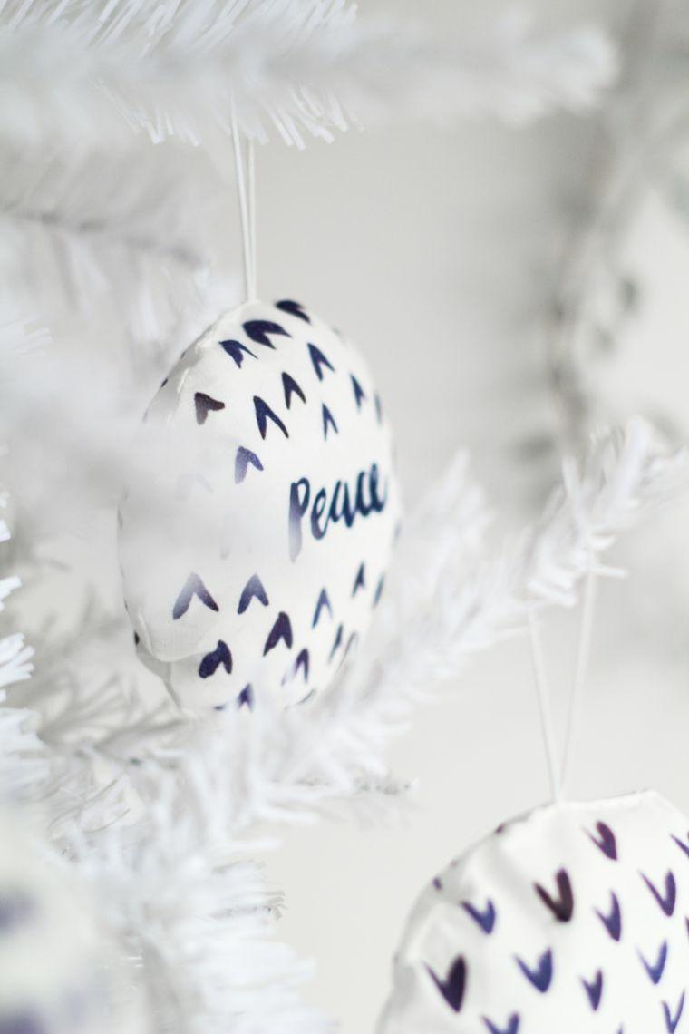 Decorazioni natalizie fai da te, palline di stoffa con ovatta all'interno appese all'albero bianco