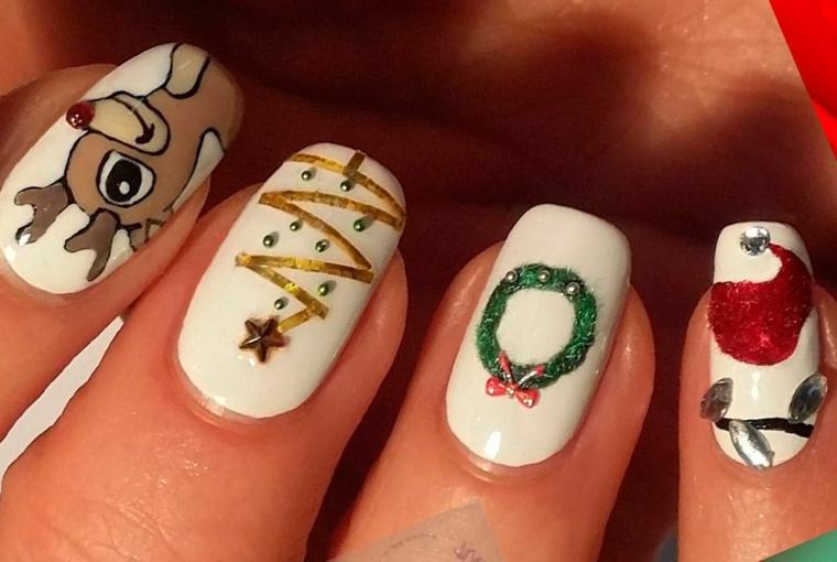 Nail art natalizie con disegno di renna e festone su una base di smalto bianco
