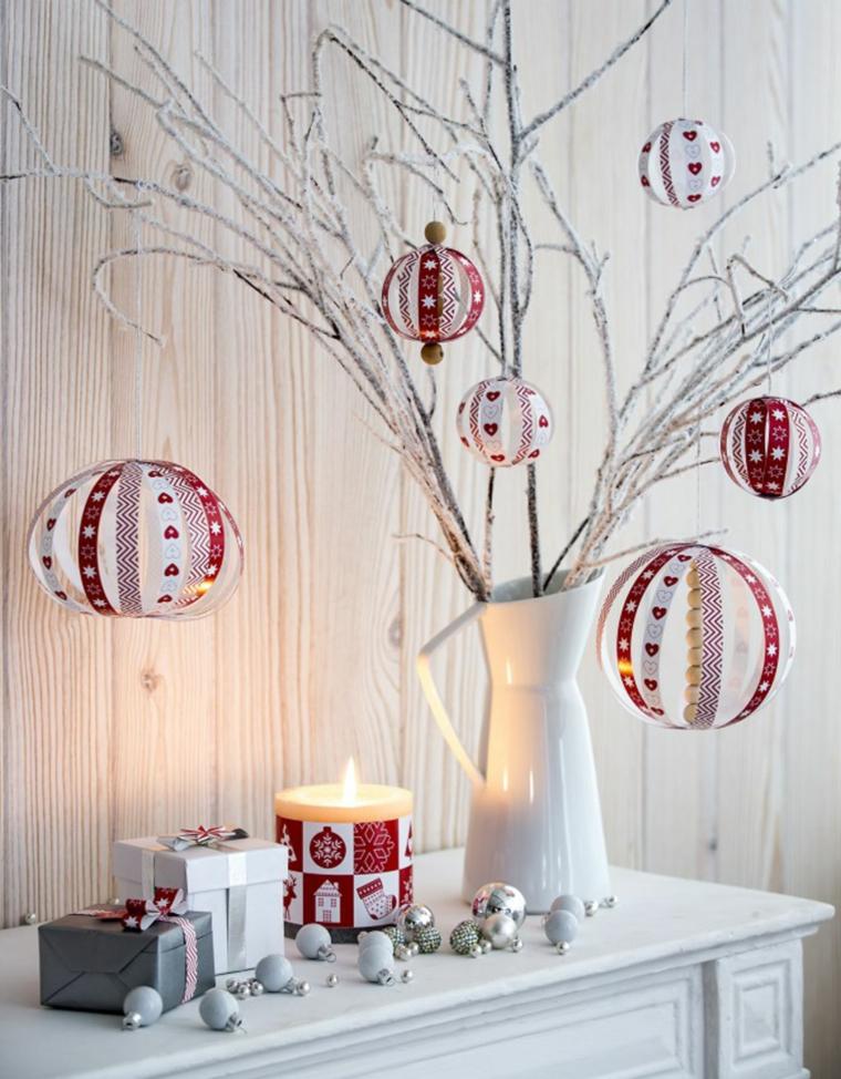 Decorazioni di carta a forma di pallina appese su un albero finto con rami