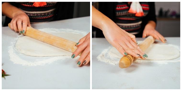 Cena della vigilia di natale, stendere l'impasto con mattarello, tavolo con farina e impasto
