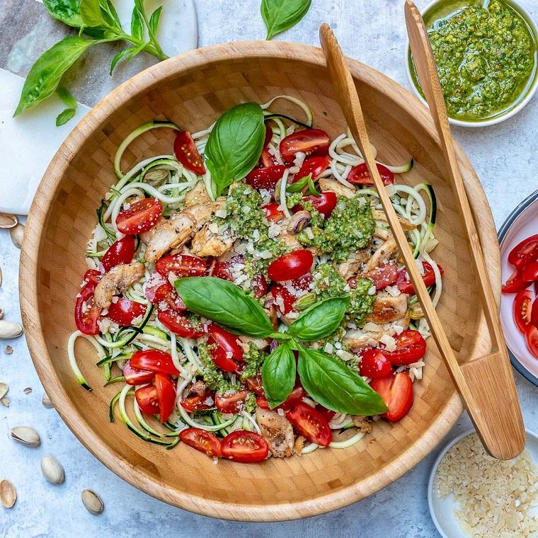 Menu Vigilia di Natale con un'insalata di gamberetti e pomodorini tagliati decorata con foglie di basilico
