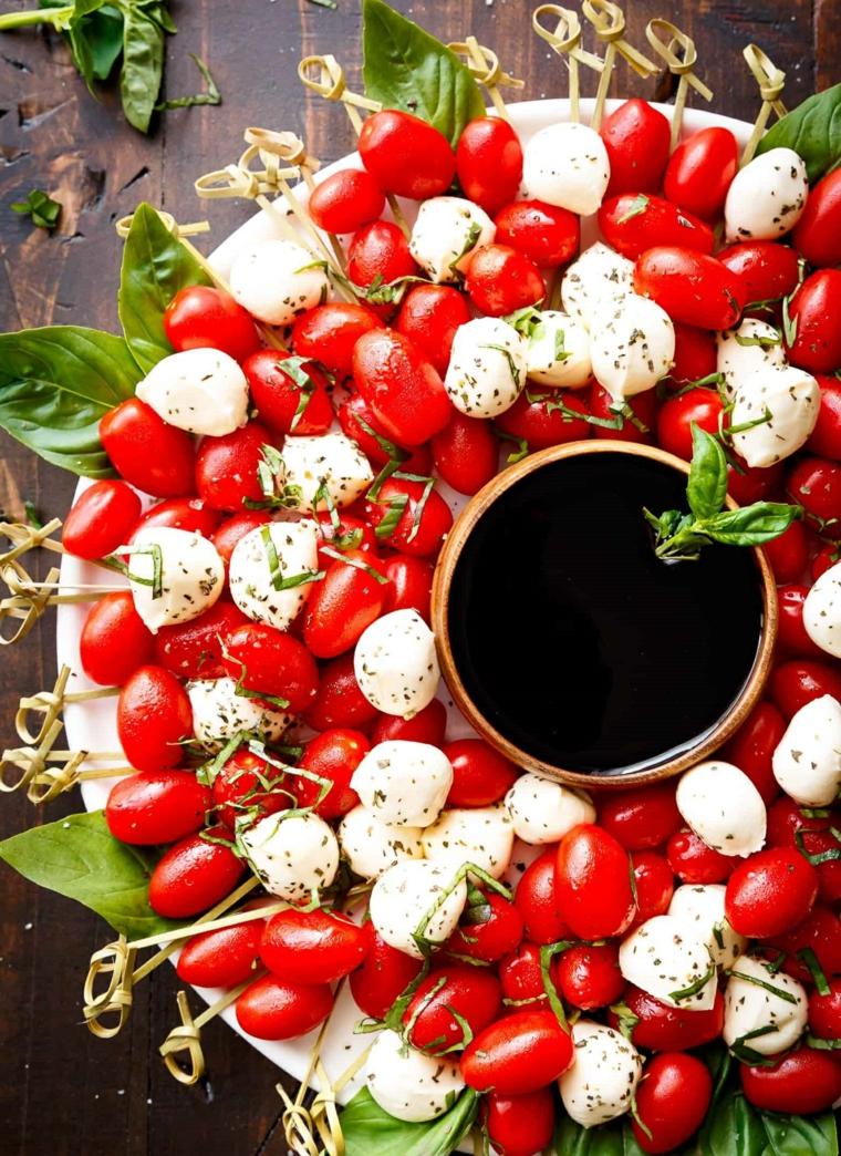 Piatto con pomodorini ciliegina e piccole mozzarelle, decorazione con foglie di basilico