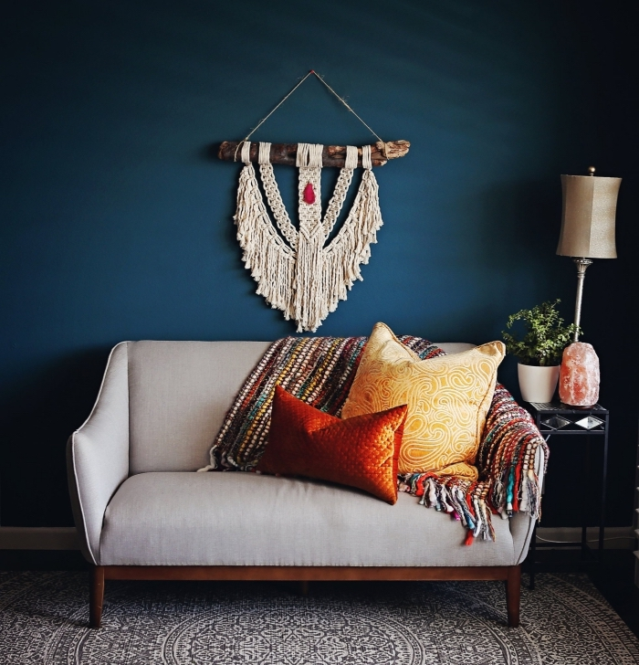 Salotto con parete di colore blu e divano grigio, decorazione rustica con macramè frange