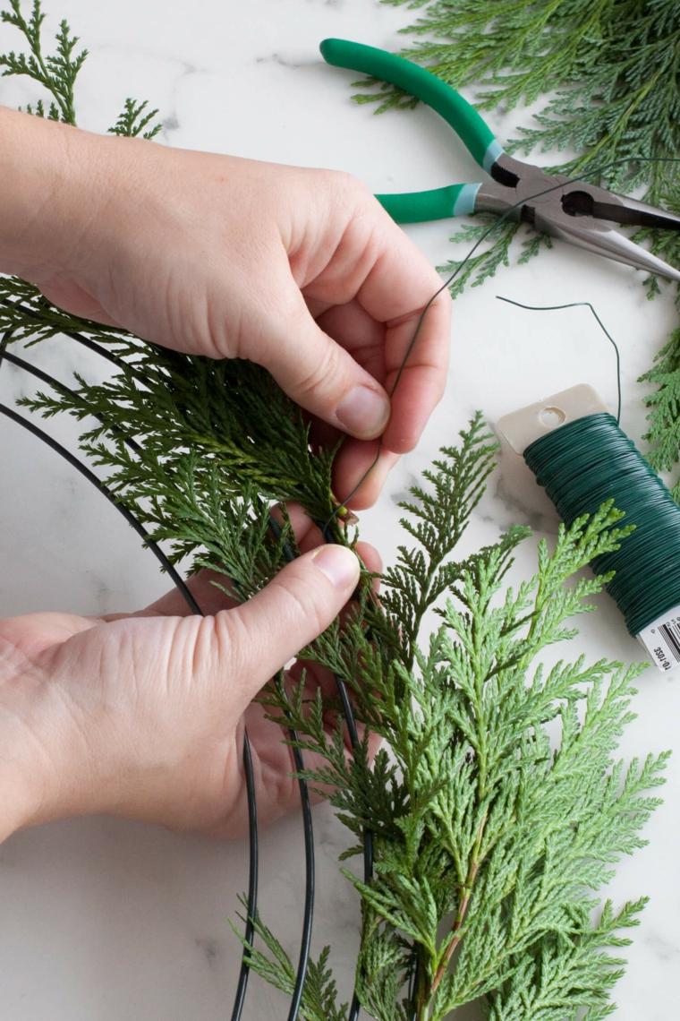 Una base di plastica per creare un festone natalizio con rametti e filo di ferro