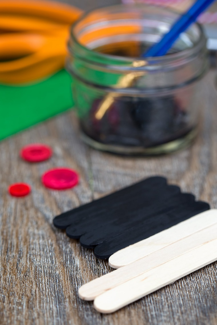 Addobbi natalizi con i bastoncini di legno dipinti di colore nero