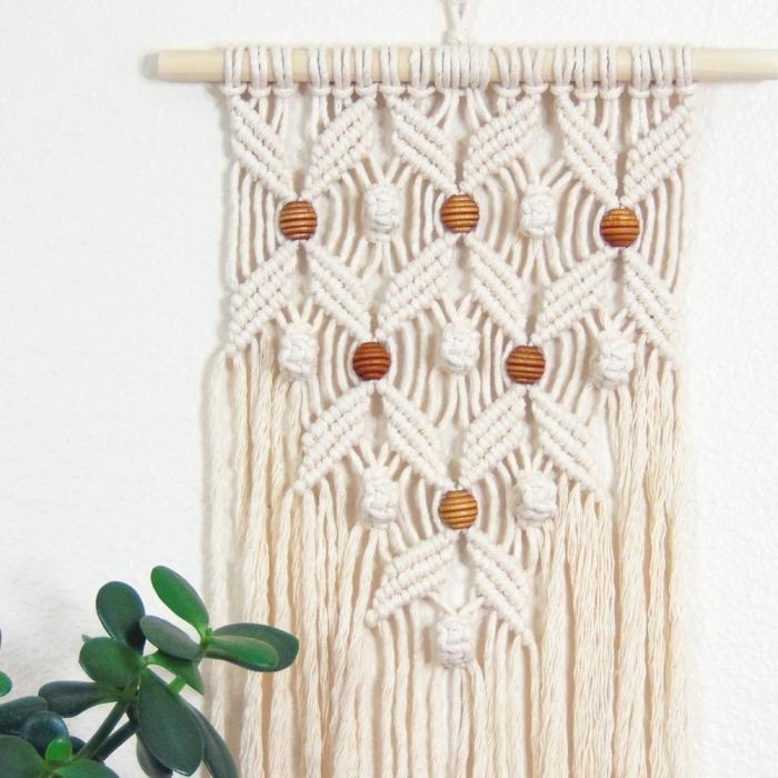 Macramè con intrecci di corda sospeso su un bastone di legno e chiodo