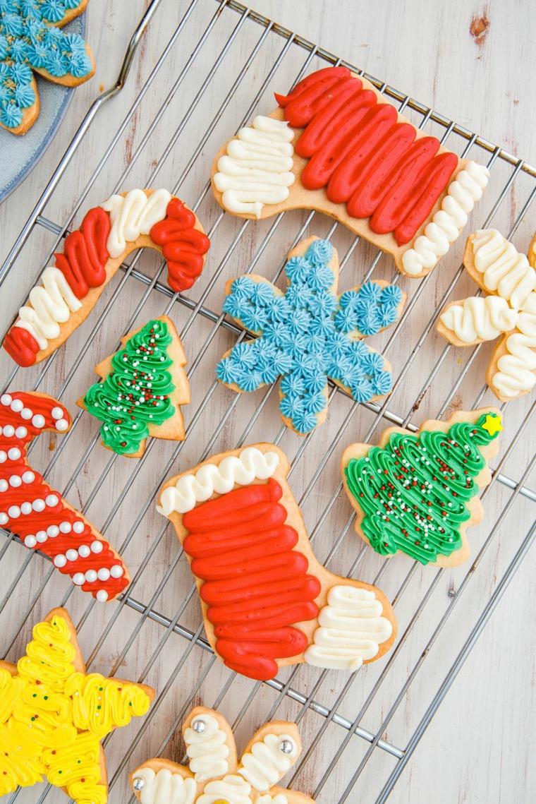 Biscotti di Natale di varie forme con una glassa reale colorata su una griglia da forno