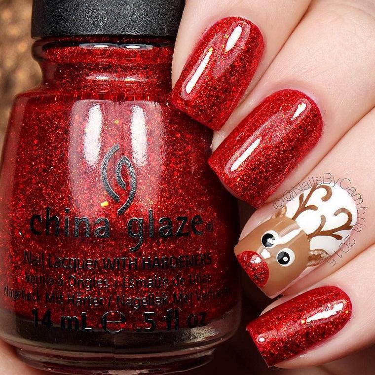 Idea per dipingere le unghie per Natale con uno smalto rosso jelly e il disegno di una renna
