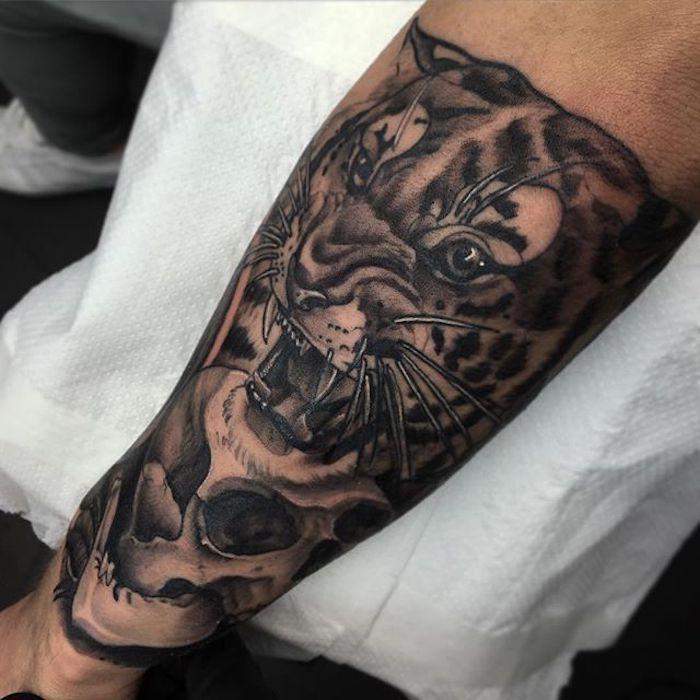 L'avambraccio di un uomo tatuato con il viso di una tigre con la bocca aperta