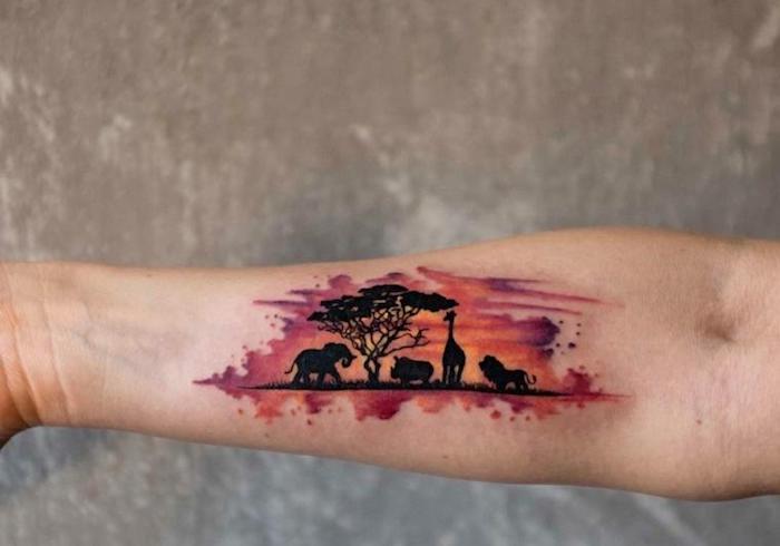 L'avambraccio di una donna con il disegno di animali nel deserto dallo sfondo colorato