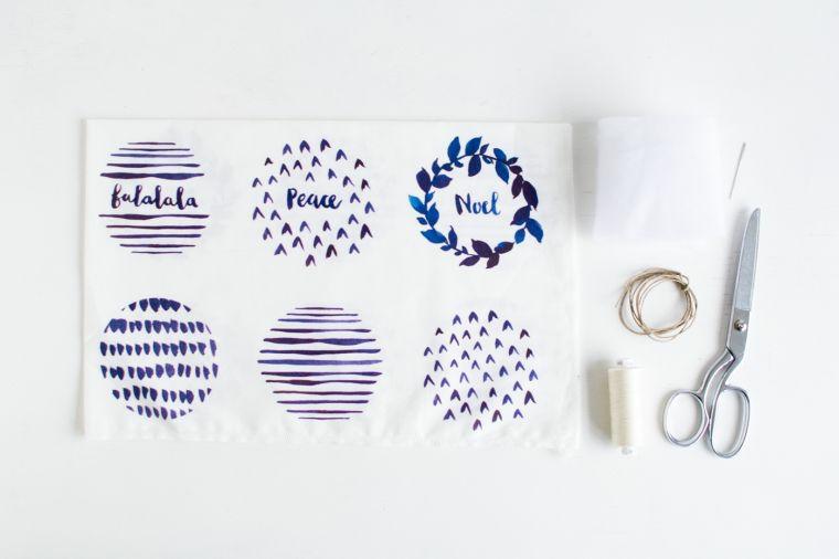 Creazioni di Natale fatte a mano con disegni e scritte su un pezzo di stoffa