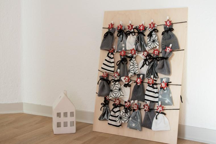Lavori natalizi fatti a mano con sacchettini appesi a dei fili su una lastra di legno