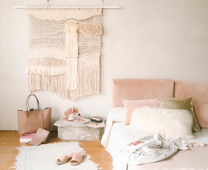 Zona notte con una testa letto di tessuto rosa e decorazione macramè fai da te