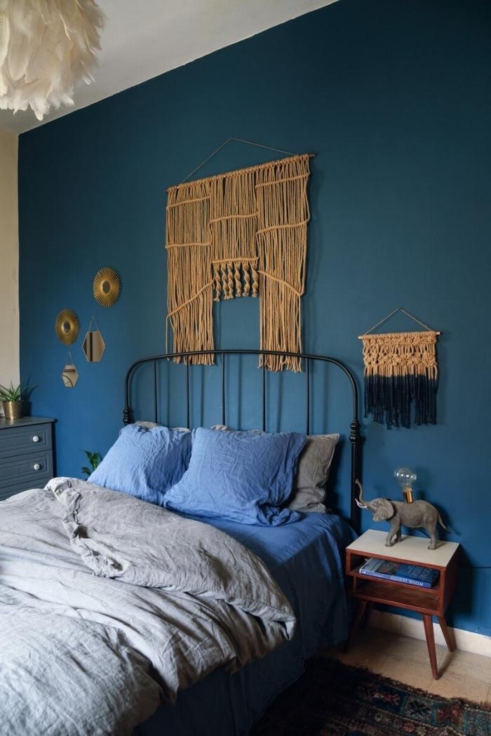 Una camera da letto con parete di colore blu e creazioni macramè con corda canapa