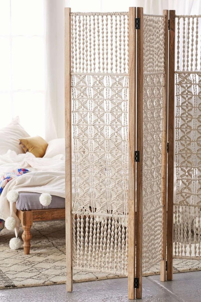 Separè di legno con tenda di macramè con intrecci, camera da letto con un tappeto etnico