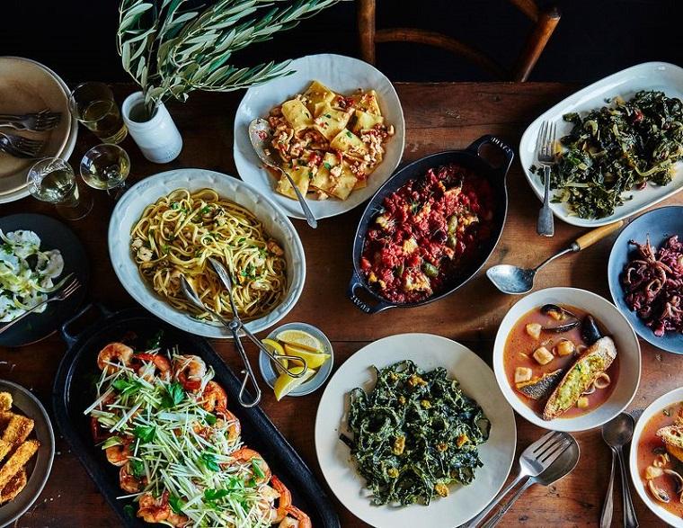 Ricette natalizie e un tavolo pieno di piatti con pesce e frutti di mare