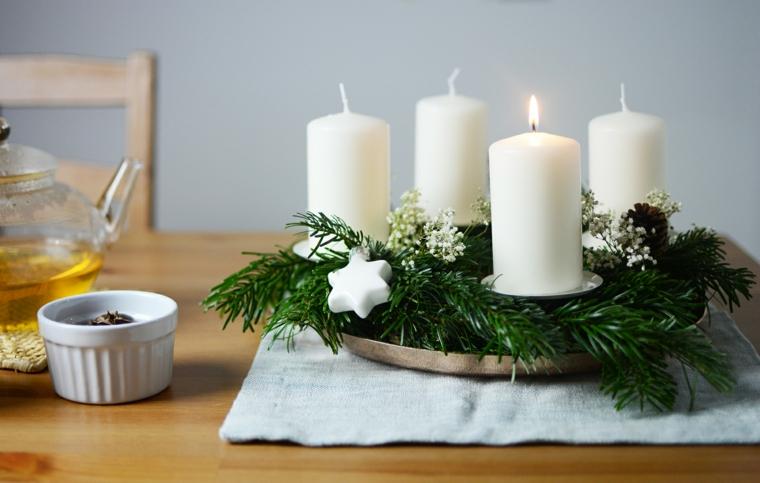Lavoretti di Natale e un'idea per un centrotavola con candele e rametti verdi dell'albero natalizio