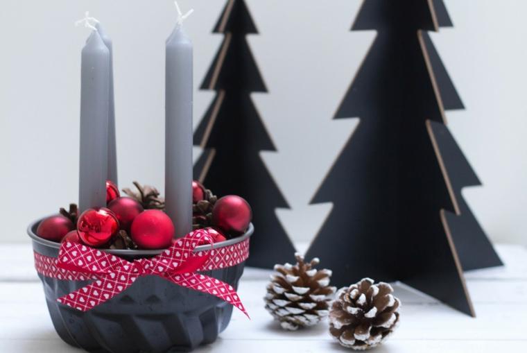 Idea per dei lavoretti di Natale con le pigne, un centrotavola con candele e fiocco rosso