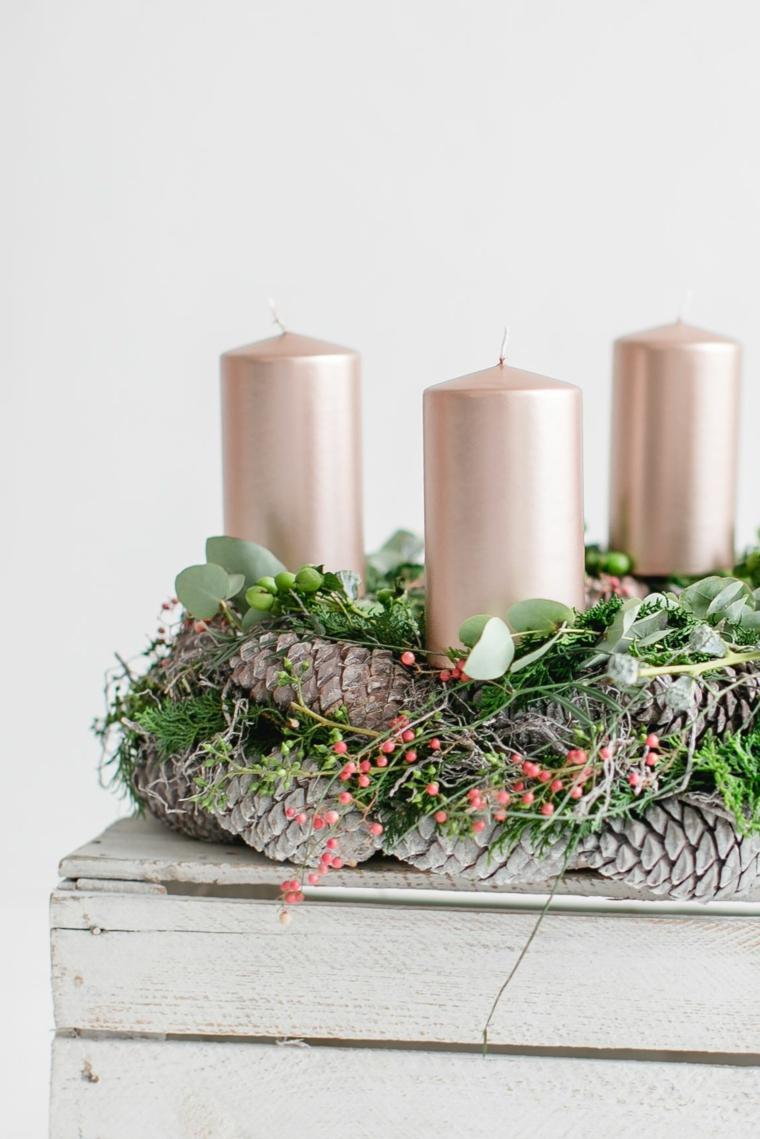 Decorazione del tavolo con un centrotavola di candele con pigne e foglie verdi