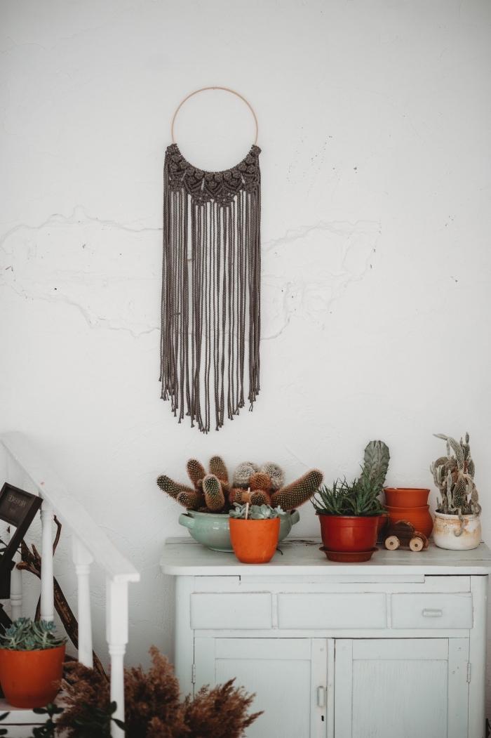 Arredo con mobili di legno in stile rétro e piante grasse, decorazione macramè di colore marrone