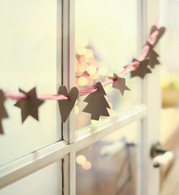 Ghirlande natalizie fai da te facili con ornamenti di carta su un filo rosso attaccati alla finestra