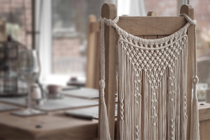 Una sedia di legno decorata con una creazione di macramè con corda bianca