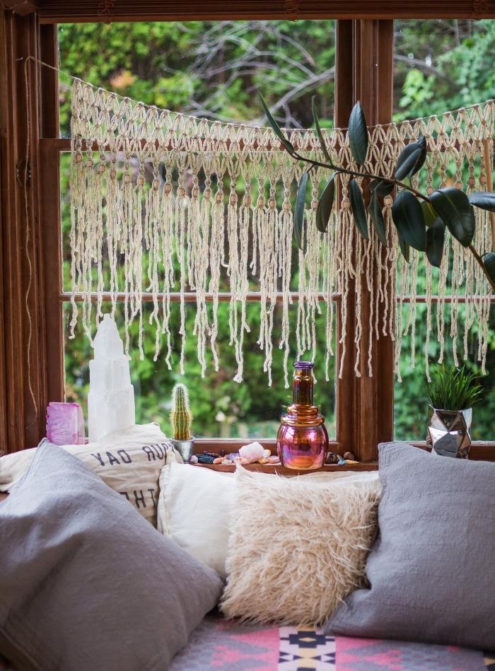 Una finestra di legno con decorazione sospesa di un macramè, divano con tanti cuscini colorati