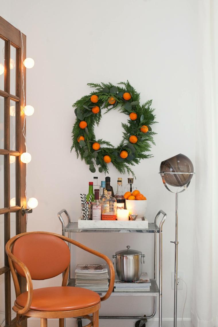 Lavoretti di Natale e un'idea con una ghirlanda di foglie e clementine